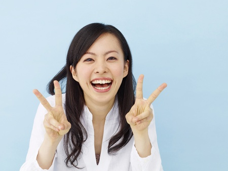 Happy young japanese girl showing victory sign isolated on blue background Zdjęcie Seryjne