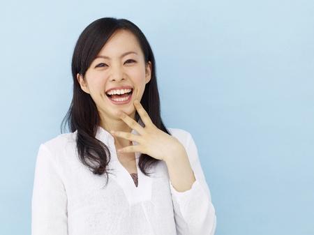 青色の背景に分離された勝利のサインを示す幸せな若い日本の女の子 写真素材