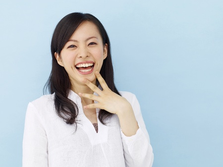 Happy young japanese girl showing victory sign isolated on blue background Stock Photo
