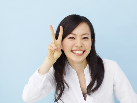Happy young japanese girl showing victory sign isolated on blue background photo