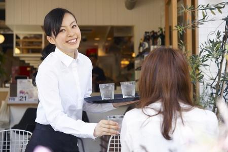 camarero: Servicio de mujer con una sonrisa Foto de archivo
