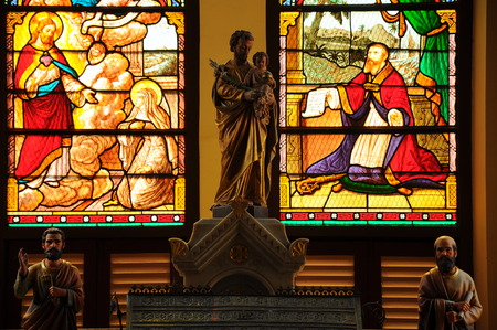 Stained-glass window behind the the Saint stutue