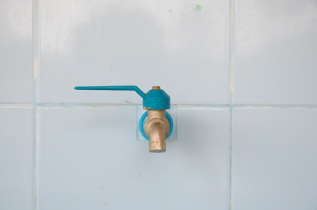 Faucet on the white tile  wall
