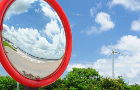 Round mirror with wind turbine in background Stock Photo