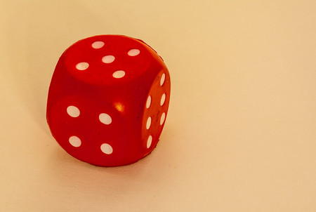 Rolling dice - red cube with white dots