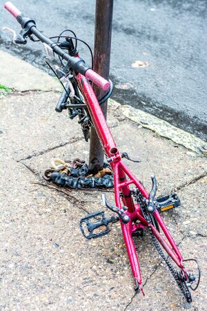 incapacitated: Retired city veteran - leashed bicycle incapacitated and chained to a pole. Red and black.