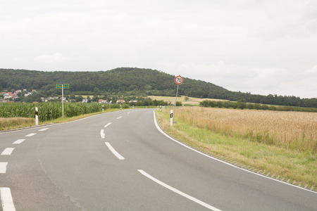 Road along the field in Bavaria, Germany - green hill, golden Wheat field and clean road.