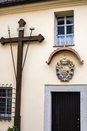 Cross on the wall of church facility in Bavaria, religious symbols above the door
