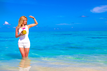 Blonde girl with coconut cocktail in her hand