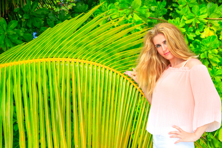 Blonde girl in front of a palm leaf