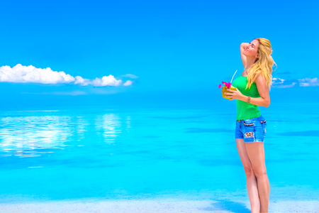 Blonde girl with coconut cocktail on a sandy beach Stock Photo