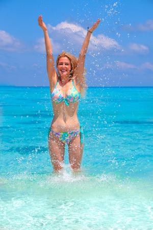 Blonde girl is jumping with turquoise bikini in the sea Stock Photo
