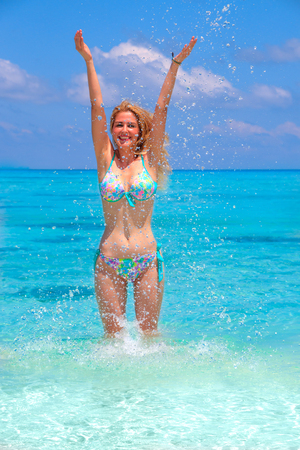 Blonde girl is jumping with turquoise bikini in the sea Standard-Bild
