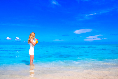 Blonde girl with coconut cocktail on the beach