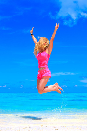 Jumping young girl on the beach in Maldives Archivio Fotografico - 98754579