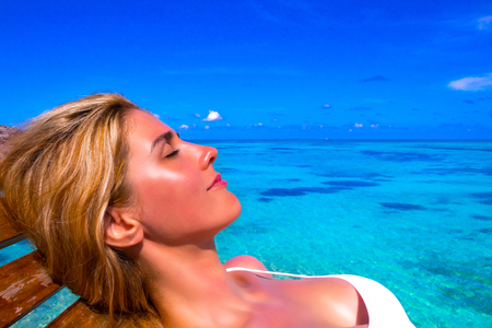 Blonde girl sunbathing on the beach in Maldives