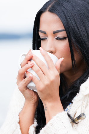 Woman drinking coffee on the beach Stock Photo