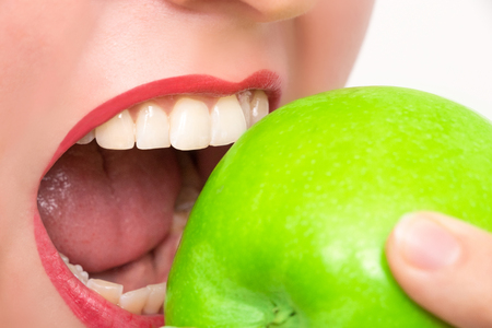 Woman bites in green apple