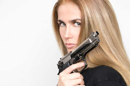 Dangerous blond woman with gun in hand 스톡 콘텐츠