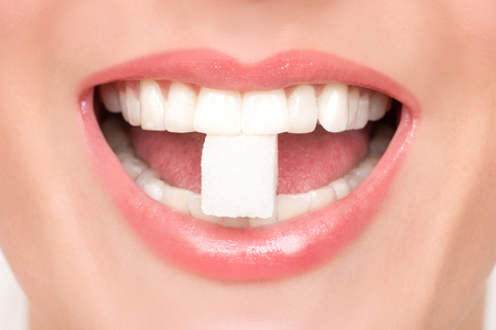 Beautiful womans mouth with big white teeth bites on a white sugar cube