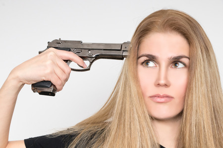 Desperate blond woman holds the gun to her head