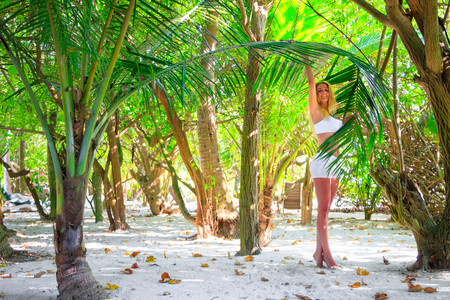 Beautiful laughing woman stands on tiptoe in the palm forest