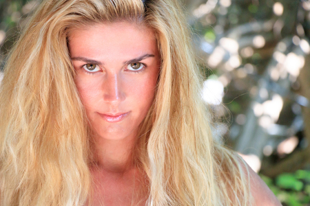 Gorgeous wild blond woman with long hair looks into the camera