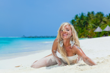 Blonde girl lying in the sand