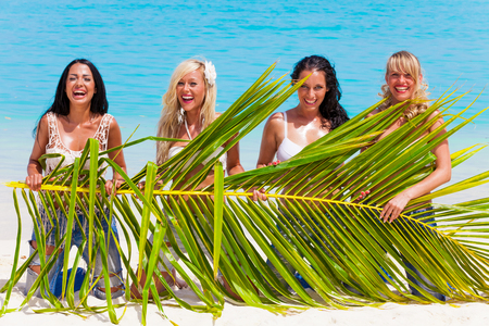 Girl group with palm leaf in her hands