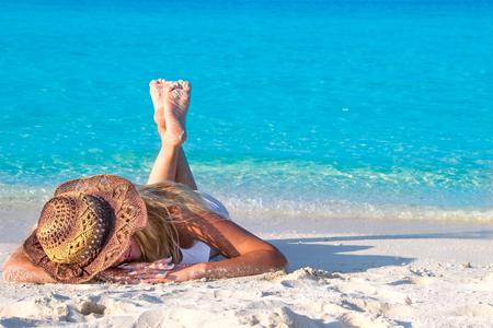 Blond kobieta leży w kapeluszu na piaszczystej plaży