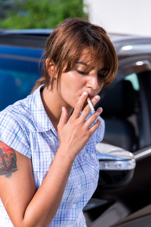 Girl is smoking in front of the car