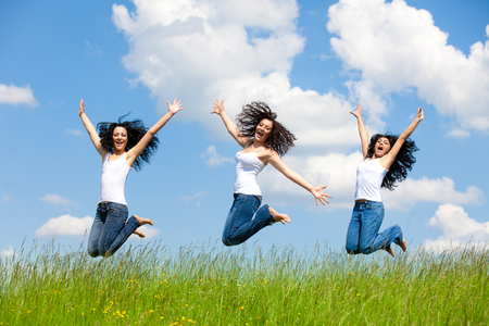 Jumping women on the meadow