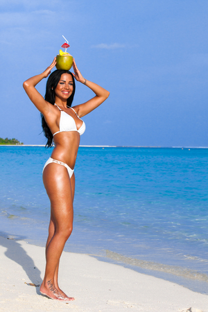 Black haired girl with coconut in her hand on the beach Stock Photo