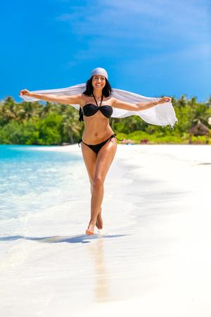 Black haired girl with black bikini in the sea on Maldives