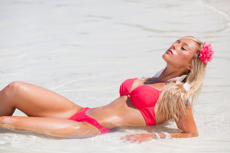 Blonde girl with red bikini in the sea on Maldives
