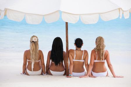 Happy young women in bikinis on summer beach Standard-Bild