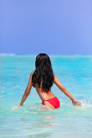 Black haired girl with red bikini in the sea on Maldives