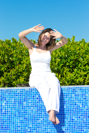 Woman sitting on pool edge Stock Photo