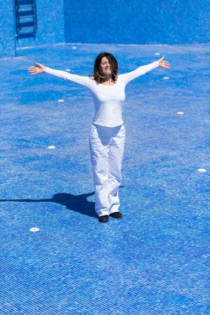 Dancing woman in the empty swimming pool