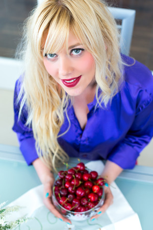 Blonde woman eating cherries