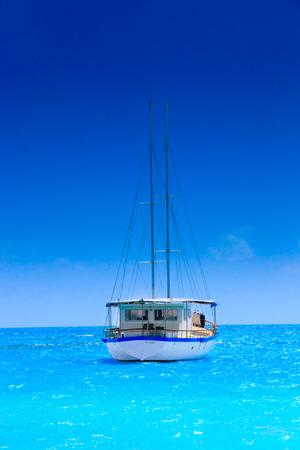 Sailing yacht in turquoise ocean near the beach