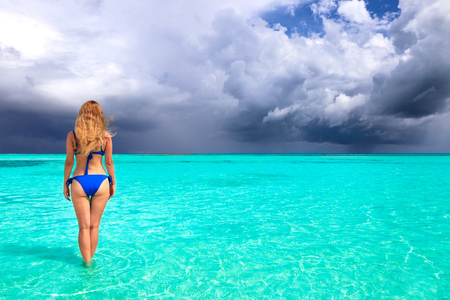 Blonde woman is standing with blue bikini in shallow water in front of an approaching storm Stockfoto