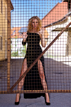 Blonde woman with black dress behind bars