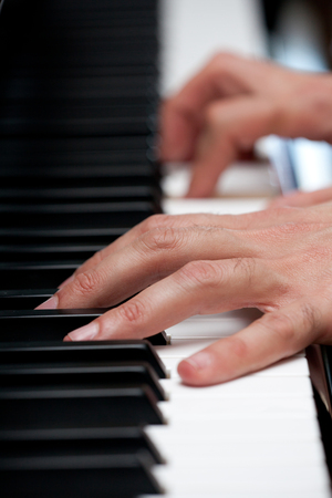 Piano keys with human hand