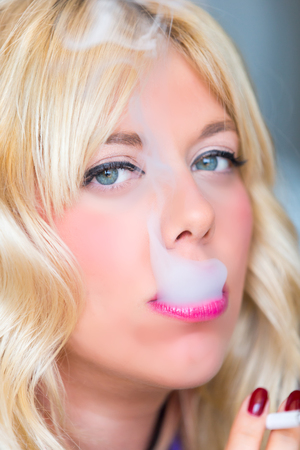 Smoking blonde woman Foto de archivo
