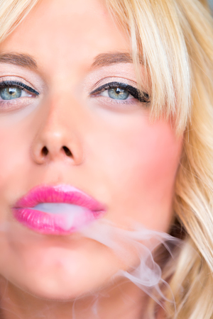 Blonde woman with cigarette in mouth