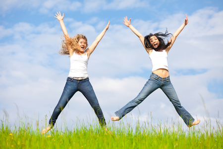 Two girls are jumping over the summer meadow