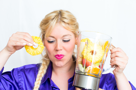 Blonde woman with a blender full of fruit Stock Photo