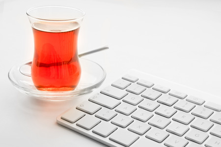 White keyboard and turkish tulips tea glass