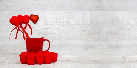 Shiny red coffee cup and red roses on wooden Standard-Bild